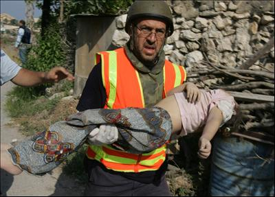 Photo:A rescuer carries a body of a child killed in Israeli air raid in Qana, 6 kilometers (4 miles) from the port city of Tyre in south Lebanon, July 30, 2006.