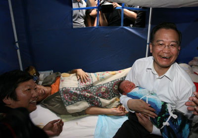 Photo:Premier Wen Jiabao holds a newborn baby in his arms at a temporary tent and shares a light moment with the child's family members when he visits quake-scarred Pu'er, Southwest China's Yunan Province June 5, 2007.