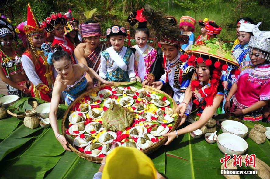 People of 26 ethnic groups in festival dresses make rice dumplings together to greet the Dragon Boat Festival at the Taiyanghe National Forest Park in Pu'er, south China's Yunnan province. (China News Service/Liu Ranyang)