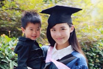 Female master poses for graduation photos with son