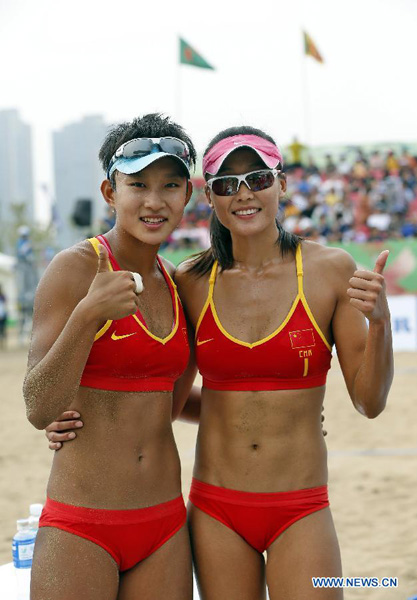 Xia Xinyi (L) and Ma Yuanyuan of China celebrate victory after the women's gold medal match of beach volleyball against Radarong Varapatsorn and Udomchavee Tanarattha of Thailand at the 17th Asian Games in Incheon, South Korea, Sept. 28, 2014. Xia Xinyi and Ma Yuanyuan won 2-0 and claimed title. (Xinhua/Shen Bohan)