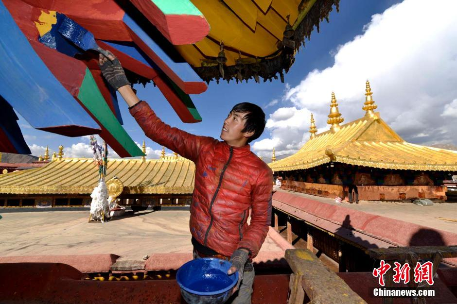A worker paints wind-resistive component under the golden roof of the temple on Oct. 28, 2014. (CNS/Li Lin)
