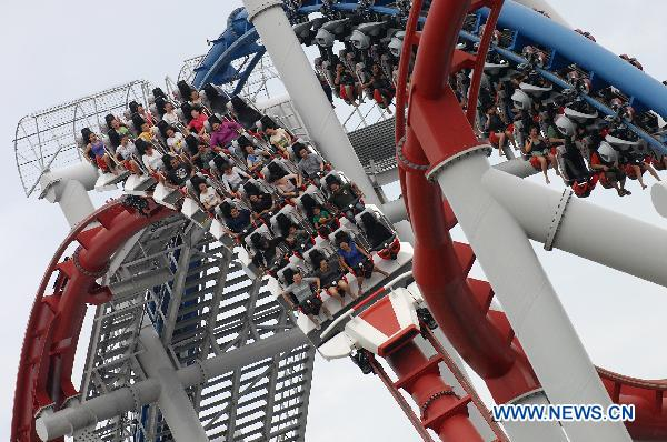 Tourists enjoy roller coaster at Universal Studios Singapore, Singapore, May 30, 2011.  [Photo:Xinhua]