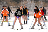 Beautiful skiers wear shorts in snow