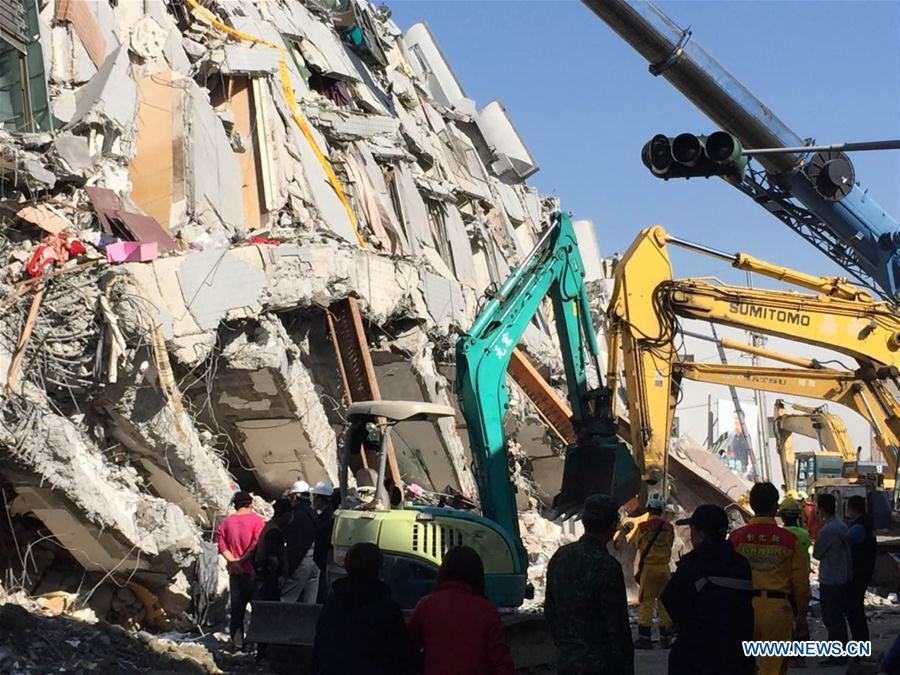 Rescuers move the debris of a car while searching for survivors at a collapsed building in Tainan City, southeast China's Taiwan, Feb. 8, 2016. Saturday's 6.7-magnitude earthquake, which struck just two days ahead of the traditional Chinese New Year near Tainan, has killed at least 40 people, all but two of them in the collapse of the 16-story residential complex. More than 100 people are believed to still be under the debris, stoking fears that the eventual toll could top 100 as the likelihood of survivors ticks away. (Photo/Xinhua)