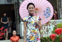 Models in cheongsams present classical oriental beauty