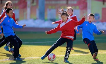 Primary school students participate in soccer training in N China