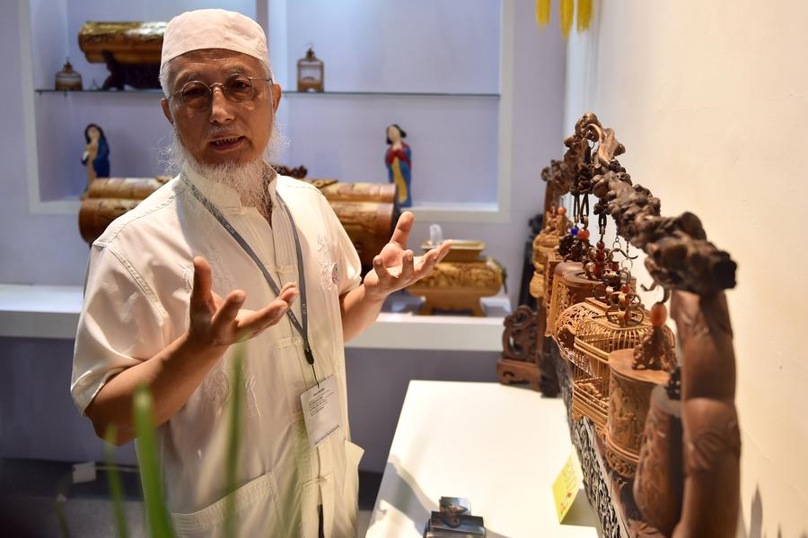 Cultural inheritor Wu Yunsheng introduces his bamboo carvings at the 13th China (Shenzhen) International Cultural Industries Fair in Shenzhen, South China's Guangdong province, May 11, 2017. The 5-day fair started on May 11, attracting 2,302 exhibitors. (Photo/Xinhua)