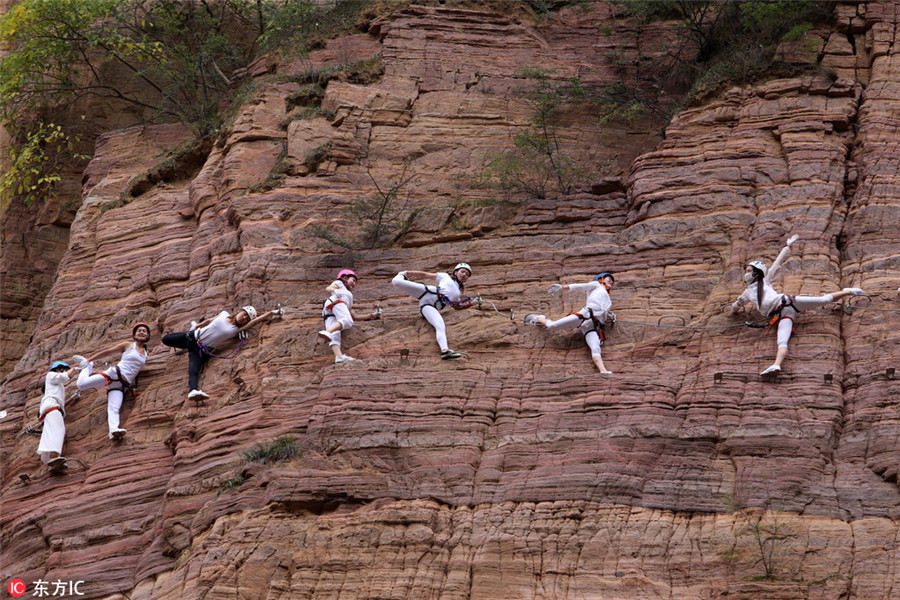 High on mountain: Yoga enthusiasts practice on cliff