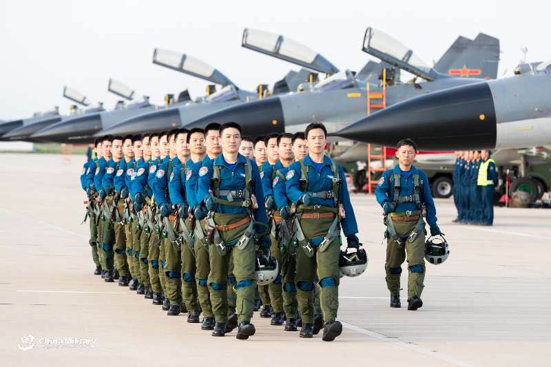 Pilots assigned to an aviation brigade of the air force with the PLA Northern Theater Command walk in formation as J-11B fighter jets sit abreast on the flightline prior to a round-the-clock flight training exercise on September 14, 2018. (eng.chinamil.com.cn/Photo by Yang Pan)