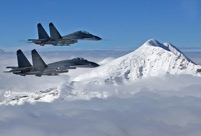 J-11B fighter jets patrol snow-covered mountain area