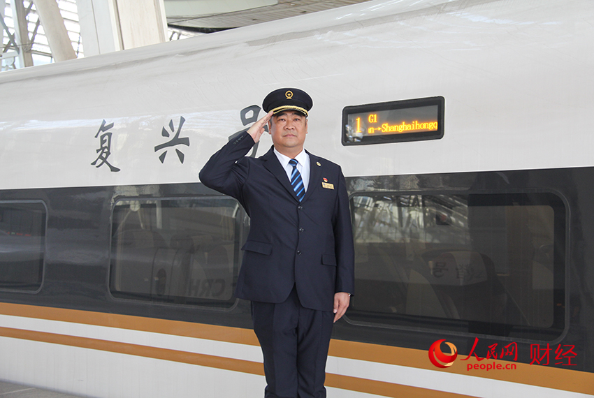 High-speed train driver Han Junjia salutes in front of a Fuxing bullet train. (Photo/Li Nanhua from People's Daily Online)