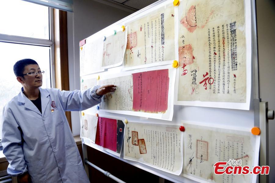Xing Jian, responsible for making replicas of valuable cultural relics, works at Qinghai Archives in Xining City, Northwest China's Qinghai Province, Nov. 14, 2019. After graduation with a major in computer sciences in 2009, Xing has been working in making replicas of cultural relics, such as a genealogy book, and he has made technical breakthroughs in this field. (Photo: China News Service/Ma Mingyan)