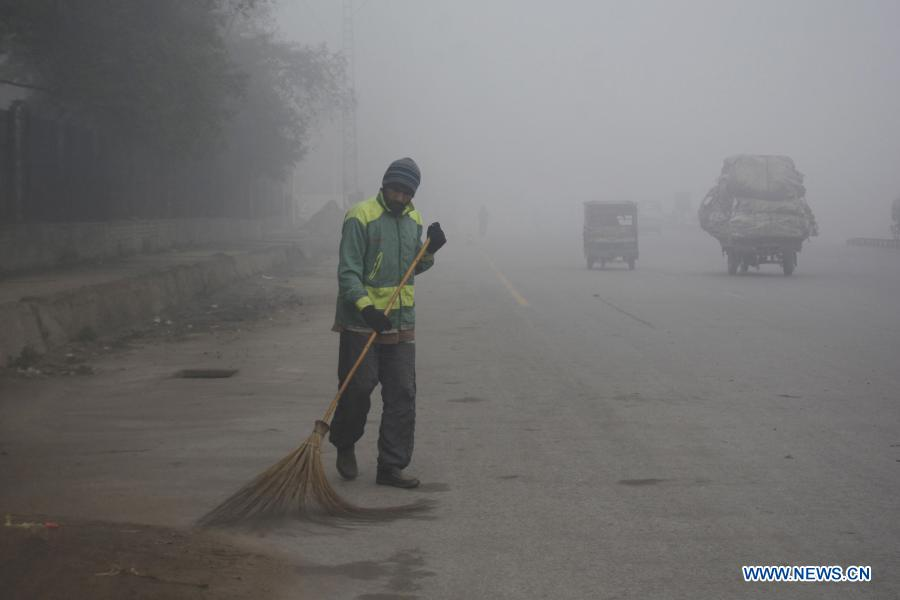 A man cleans a road amid heavy fog in Lahore, capital of Pakistan's Punjab province on Jan. 19, 2021. Dense fog shrouded several cities in Pakistan on Tuesday. (Photo by Sajjad/Xinhua)