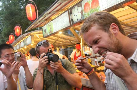 Tourists try Chinese snacks at Donghuamen night fair in Beijing
