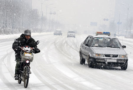 Vehicles run in snow on a snow-covered road in Shenyang.