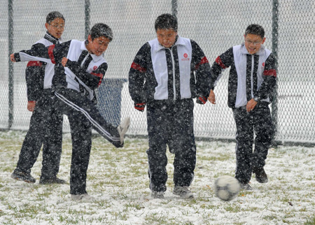 Students play soccer in snow in Beijing, capital of China, Nov. 12, 2009