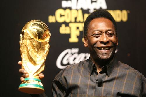 Pele poses with FIFA's World Cup trophy, on display in Brazil
