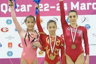 Silver medalist China's Huang Qiushuang, gold medalist China's Wu Liufang and bronze medalist Turkey's Goksu Uctas pose on the podium during the women's floor exercises event at the Doha Gymnastics World Cup at Aspire Academy in Doha, capital of Qatar, March 24, 2010.