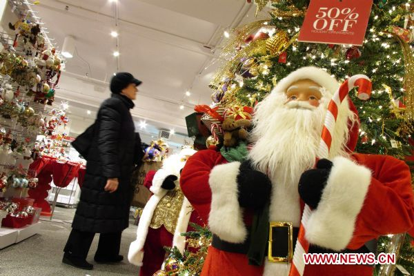 A woman selects Christmas decorations at Lord & Taylor Department Store in New York, the United States, Dec. 17, 2010. As Christmas approaches ...