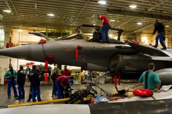 Frenchmen work on jets on Charles de Gaulle aircraft carrier