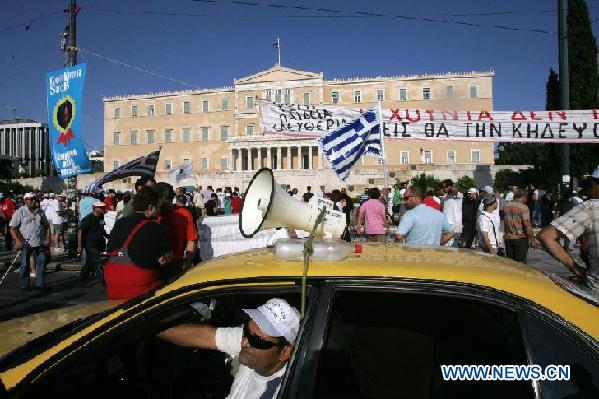 Greek taxi drivers protest in front of parliament building in Athens