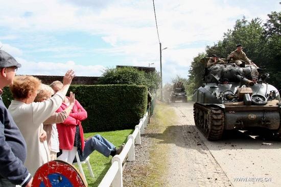 People waves to armed vehicles driven by military fans in an activity held to simulate the liberation of Mons, Belgium, Aug. 28, 2011. About 100 heavy equipped vehicles collected by military fans from Belgium, France, Germany, the Netherlands and Switzerland arrived in Mons on Sunday, to reproduce the appearance of liberation of Mons in World War II in 1944. More than 2,000 people attended the activity. (Xinhua/Wang Xiaojun)
