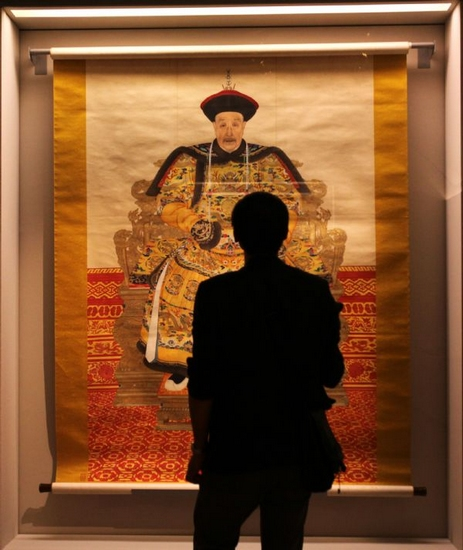 A visitor watches a portrait of Emperor Kangxi in the Louvre Museum in Paris, capital of France, on Sept. 26, 2011. About 130 artifacts from the Forbidden City, China's ancient imperial palace museum, started to greet the French public in the Louvre Museum on Monday in an exhibition that will run until Jan. 9, 2012. (Xinhua/Gao Jing)