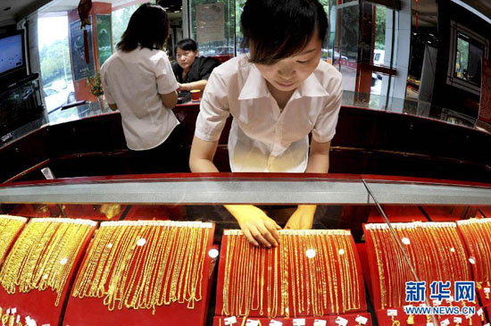 An employee at a gold store in Yiwu, located in east China's Zhejiang province, shows gold jewelry on Monday.(Xinhua/Zhang Jiancheng)