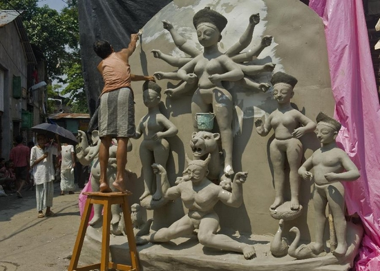 An Indian artist colours clay idols of Goddess Durga for the upcoming Durga Puja festival in Calcutta, capital of eastern Indian state West Bengal on Sept. 27, 2011. The festival celebrates the homecoming of Mother Goddess Durga and the victory of good over evil, dramatized by the goddess' demolition of the evil buffalo demon, Mahishasura. (Xinhua/Tumpa Mondal)