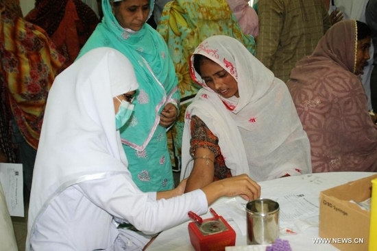 A doctor takes blood sample of a girl for the dengue virus test at a hospital in east Pakistan's Lahore on Sept. 28, 2011.  (Xinhua Photo/Sajjad)