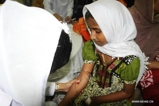 A doctor takes blood sample of a girl for the dengue virus test at a hospital in east Pakistan's Lahore on Sept. 28, 2011. The death toll as a result of Pakistan's dengue fever outbreak continues to rise at alarming rates as at least 108 people have now been confirmed dead. The total number of people who have contracted the virus is reported to be at least 10,585 in Punjab, with 9,000 reported from Lahore. (Xinhua Photo/Sajjad)