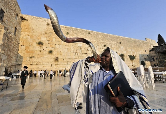 A Jew from Port Harcourt of Nigeria blows a shofar at the Western Wall Plaza in Jerusalem's Old City on Sept. 28, 2011, ahead of Rosh Hashanah, the two-day Jewish new year which will begin at sunset on Sept. 28 and conclude at nightfall on Sept. 30. (Xinhua/Yin Dongxun)