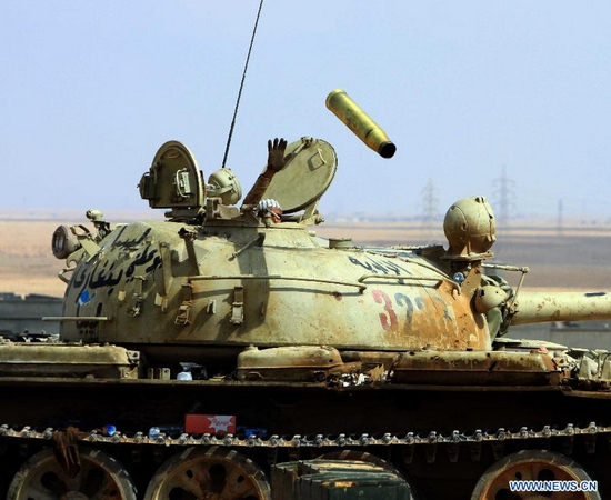 A militant loyal to the Libyan National Transitional Council (NTC) waves in a tank near Bani Walid, one of the pro-Muammar Gaddafi strongholds, on Sept. 28, 2011. (Xinhua/Hamza Turkia)