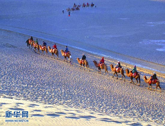 On Sept. 28, tourists travel around the Mingshashan Scenic Area in Dunhuang, Gansu province by camel. (Xinhua/ Zhang Weixian)