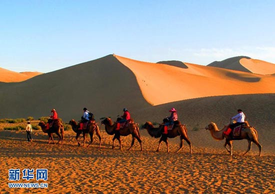 On Sept. 28, tourists travel around the Mingshashan Scenic Area in Dunhuang, Gansu province by camel. With the National Day vacation right around the corner, more and more tourists from home and abroad are going to Dunhuang. Riding on a camel, they travel in the desert to enjoy the cities rare form of natural scenery. (Xinhua/Zhang Weixian)