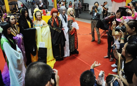 Visitors take photo of cosers in the third Western China Animation Comic Game (ACG) Festival in Chongqing Municipality, Sept. 29, 2011. The festival includes activities such as cosplay show, Hip-pop competition, forum and exhibitions. (Xinhua/Li Jian)