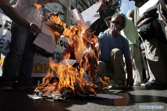 Greek artists burn copies of emergency tax notices during a protest against austerity measures in Athens, Greece, on Sept. 29, 2011. The Greek government is facing a new wave of protests as it introduces new austerity measures to obtain the sixth tranche of aids necessary to overcome the acute debt crisis.(Xinhua/Marios Lolos)