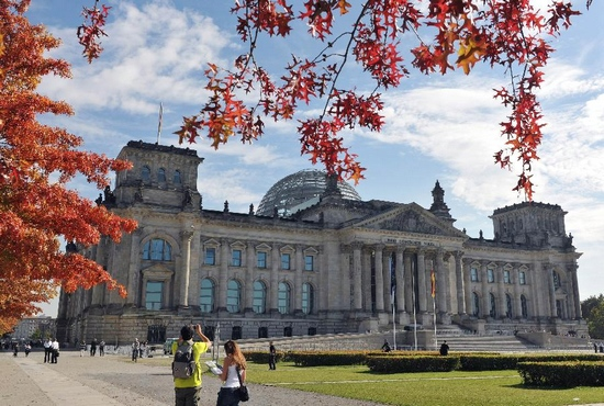 Tourists walk in front of the Reichstag building in Berlin, capital of Germany, Sept. 29, 2011. Fine weather on Thursday added to the mood of outdoor leisure for residents and tourists in Berlin. (Xinhua/Ma Ning)