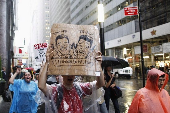 Demonstrators from the Occupy Wall Street campaign hold placards as they march in the financial district of New York September 29, 2011. After hundreds of protesters were denied access to some areas outside the New York Stock Exchange on September 17, demonstrators set up a rag-tag camp three blocks away. Zuccotti Park is a campground festooned with placards and anti-Wall Street slogans. The group is adding complaints of excessive police force against protesters and police treatment of ethnic minorities and Muslims to its grievances list, which includes bank bailouts, foreclosures and high unemployment. (Xinhua/Reuters Photo)