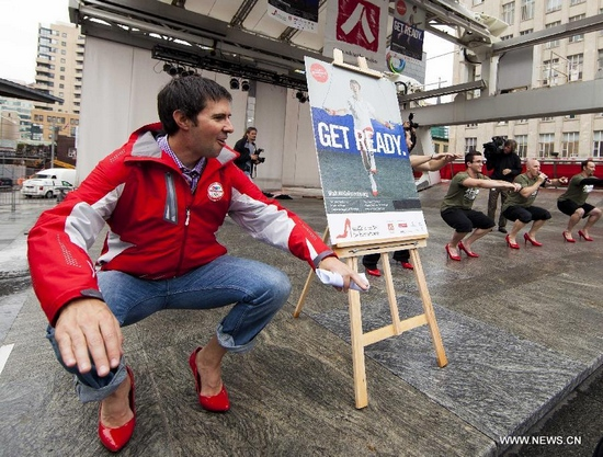 Paritipants wearing high-heel shoes try to squat during the 3rd annual Walk a Mile in Her Shoes, an event when men literally walk in women's shoes to raise awareness about ending violence against women, at Yonge-Dundas Square in Toronto, Canada, Sept. 29, 2011. (Xinhua/Zou Zheng)