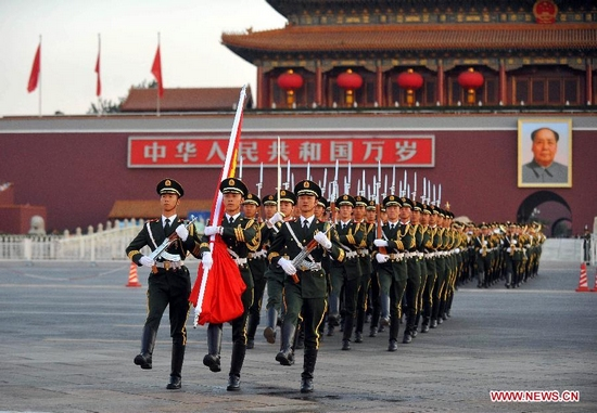 Chinese national flag guards escort the flag across the Chang'an Avenue in Beijing, capital of China, Oct. 1, 2011. More than 120,000 people gathered at the Tian'anmen Square to watch the national flag raising ceremony at dawn on Oct. 1, in celebration of the 62th anniversary of the founding of the People's Republic of China. (Xinhua/Luo Xiaoguang)