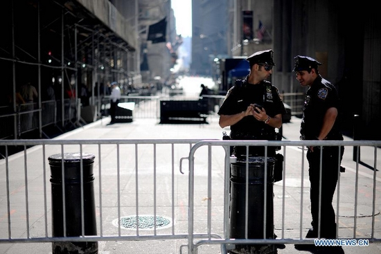 A policeman stands next to the barrier at the entrance of Wall Street in New York, the United States, Sept. 30, 2011. Police set up the fences to keep away the demonstrators of the Occupy Wall Street campaign. (Xinhua/Shen Hong)