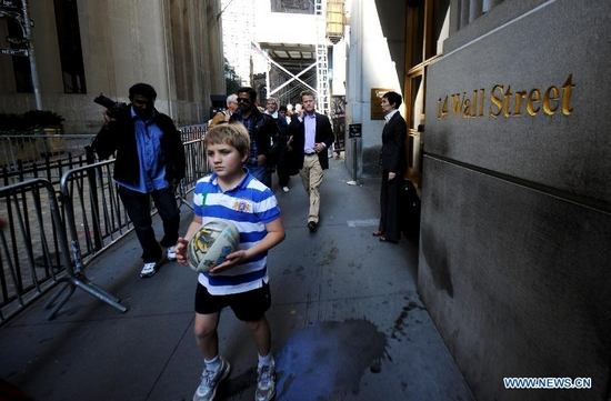 Pedestrians walk along the barrier set by police on Wall Street in New York, the United States, Sept. 30, 2011. Police set up the fences to keep away the demonstrators of the Occupy Wall Street campaign. (Xinhua/Shen Hong)