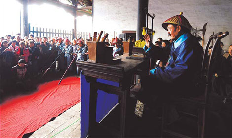 Tourists watch a performance about an ancient court trial. (Photo/Xinhua)