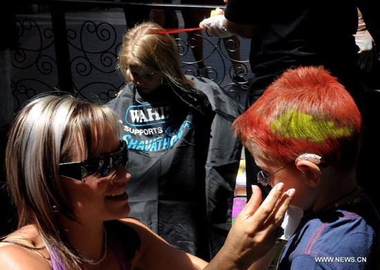 A woman looks at the colored hair on a child's hair during a charity activity for cancer patients in Pretoria, March 3, 2012. The Cancer Association of South Africa held the 2012 Shavathon from March 1 through 4, encouraging companies and individuals to shave or spray their hair to support cancer survivors.(Xinhua/Li Qihua)