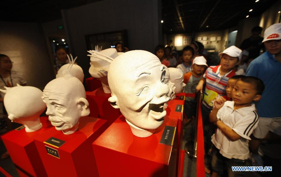 Children view statues of cartoon characters at the Shanghai Animation and Comics Museum in Shanghai, east China, Aug. 16, 2012. Various cartoons, manuscripts and technologies were presented at the museum, attracting numerous visitors. (Xinhua/Pei Xin)