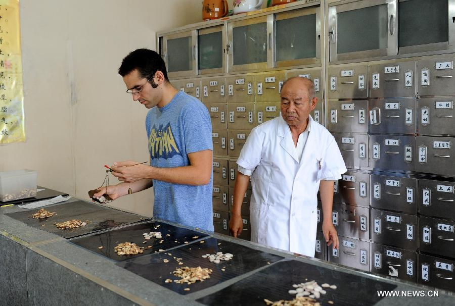 Bryan Anker (L), a student majoring in globalization from University of California, distributes Chinese herbs in accordance with prescription under guidance of traditional Chinese medicine (TCM) doctor Du Chunqing (R) at Shuita Street Community Heath Service Center in Yaodu District of Linfen City, north China's Shanxi Province, Aug. 17, 2012. (Xinhua/Yan Yuepeng)