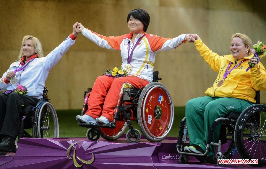 Gold medalist, Zhang Cuiping (C) of China, silver medalist, Manuela Schmermund (L) of Germany, bronze medalist, Natalie Smith of Australia celebrate during the awarding ceremony for the final of the Women's R2-10m Air Rifle Standing-SH1 shooting event at London 2012 Paralympic Games in London, Britain, on Aug. 30, 2012. Zhang took the gold medal with 500.9 rings. (Xinhua/Wang Haofei)