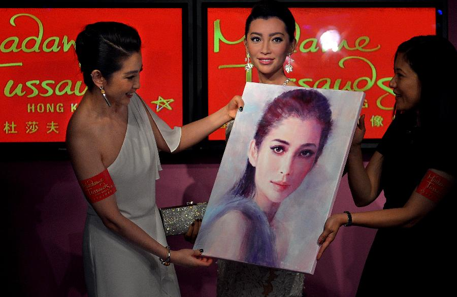 Chinese actress Li Bingbing (L) holds her portrait at the unveiling ceremony of her wax figure at the Madame Tussauds museum in Hong Kong, south China, Sept. 6, 2012. She also has the other wax figure exhibited at the Madame Tussauds in Shanghai. (Xinhua/Chen Xiaowei)